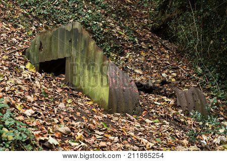 Ruined Anderson shelter rusted and partially buried. World War Two bomb shelter showing exposed corrugated iron sheets and steel plates