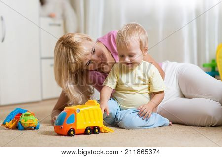Mom and her toddler son plays with car toys in his cosy childrem room
