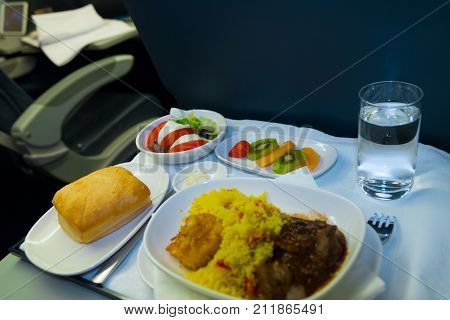 Food served on board of business class airplane on the table. Tray of food in the airplane. Tray of food on the plane business class travel. Prepared food on the plane