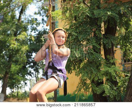 Cute girl having fun in adventure park