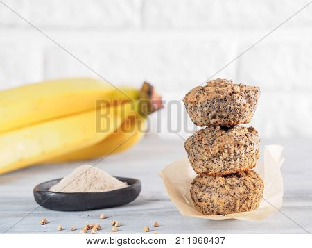 Healthy gluten-free homemmade banana muffins with buckwheat flour. Stack of three vegan muffins with poppy seeds on gray wooden table. Copy space