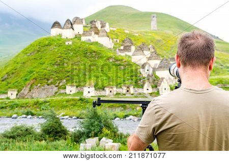 Back view male outdoor photographer takes pictures of crypts of City of the Dead in republic of North Ossetia, Russia