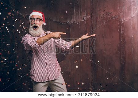 Happy bearded and modern man in Santa's hat and in fashionable glasses shows his fingers to the side and happy smile in gold confetti. Happy New Year 2018 and modern party with fashion Santa