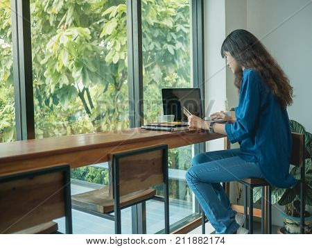 Asian young woman using laptop computer to pay shopping online pay the bill online at coffee shop.