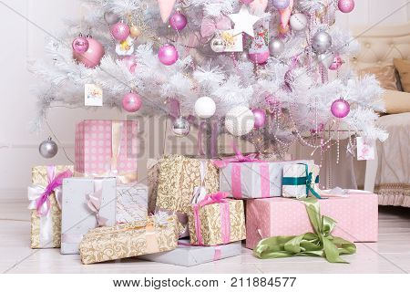 Giftboxes pink and white christmas decorations balls hanging on a decorative white christmas tree. Concept New Year celebration background.