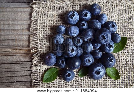 Freshly picked blueberries on a burlap cloth background.Fresh organic blueberry. Bilberries.Healthy eating,vegan diet or raw food concept.