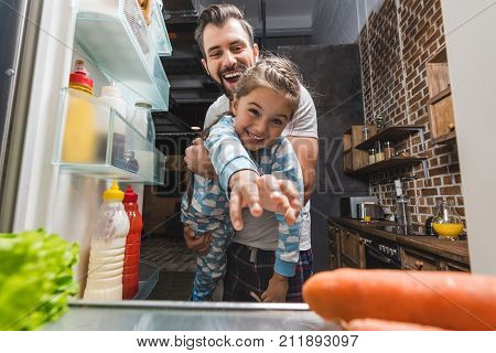 Father With Daughter Trying To Reach For Food