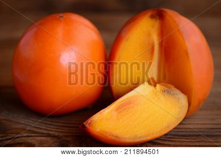Sweet fresh persimmon on a brown wooden table. Slices persimmon photo. Delicious winter fruits. Source of beta-carotene, dietary fibre and minerals. Closeup