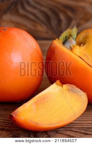 Ripe fresh persimmon on a brown wooden background. Slices persimmon photo. Tasty winter fruits. Source of beta carotene, dietary fiber and minerals. Closeup