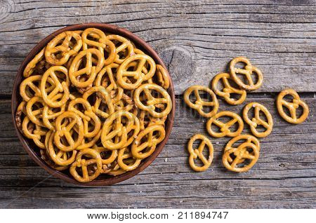 Pretzels in bowl on wooden background . Photo of snack