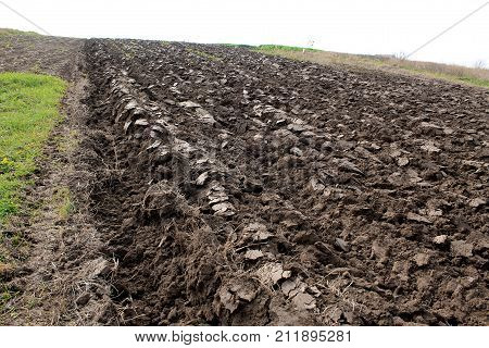 Plowed field with Ukrainian chernozem on hillside. Furrows are visible.
