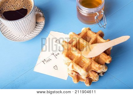 Waffles with honey and miss you message - Tasty fresh waffles with honey on top a cup of hot coffee and a cute note on a piece of paper with the miss you message and hearts on a blue wooden table.