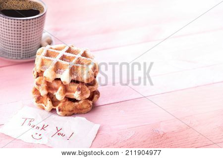Cute thank you note and dessert - Savory snack with freshly baked waffles covered with powdered sugar a mug of coffee and a scribble with thank you and a smiley face on a pink background.