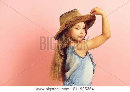 Girl in fancy outfit holds cowboy hat. Fashion and casual style concept. Little lady in stylish clothes on pink background copy space. Kid with confident face and long fair hair wears jeans dress