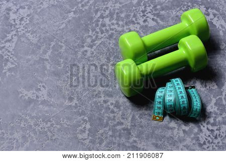 Measuring Tape Roll Next To Plastic Barbells. Workout And Measurement