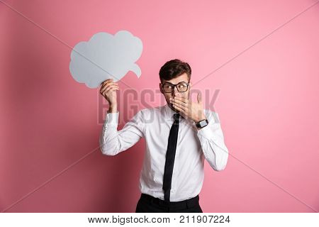 Portrait of a shy embarrassed man in white shirt and eyeglasses covering his mouth with hand while holding blank paper speech bubble above his head isolated over pink background