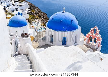 Oia Santorini - Greece. Famous attraction of white village with cobbled streets Greek Cyclades Islands Aegean Sea.