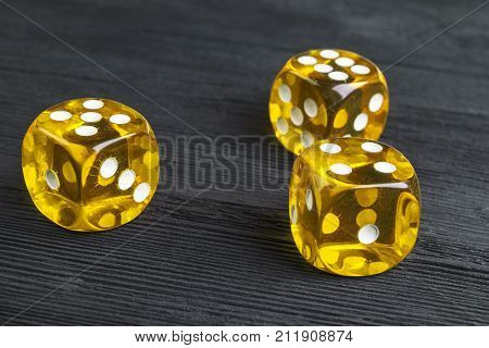 risk concept - playing dice at black wooden background. Playing a game with dice. Yellow casino dice rolls. Rolling the dice concept for business risk chance good luck or gambling