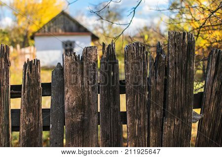 Old small white house fenced with an old wooden fence in the style of ancient Ukrainian traditions. Ruined time fence