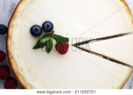 Homemade cheesecake with fresh berries and mint for dessert - healthy organic summer dessert pie cheesecake. Cheese cake