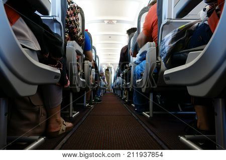 Passenger cabin in flight with people. Economy class. View from floor.