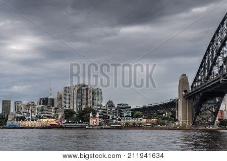 Sydney Australia - March 22 2017: Colorful Luna Park attractions on shore with towers of Kirribilli condominium district in the back. Large part of Harbour Bridge. All under heavy dark cloudscape.