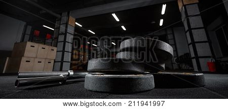 Selective focus on weights and gym equipment on the floor at crossfit box weightlifting fitness box training exercising space interior dark brutal motiovation determination concept