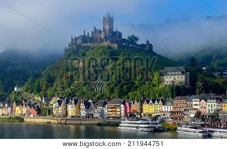 View of Cochem Germany from River with Brightly Colored Buildings and Castle On Top of Hill