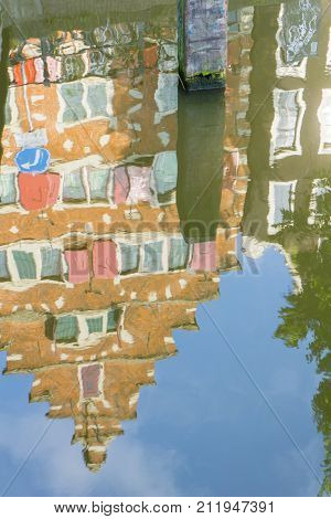 Refected architecture Amsterdam gable facade on row houses reflections rippling in canal.