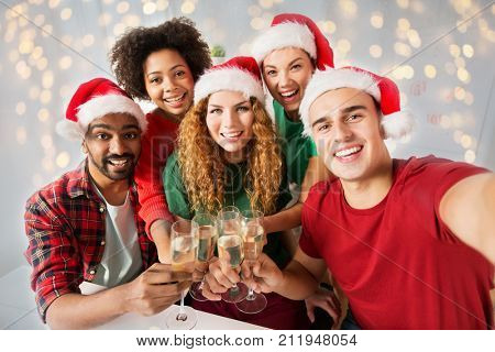 christmas, celebration and holidays concept - happy friends in santa hats clinking glasses of non-alcoholic sparkling wine at home party over lights background