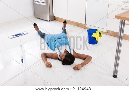 Unconscious African Housewife Lying On Floor With Bucket And Mop In Kitchen