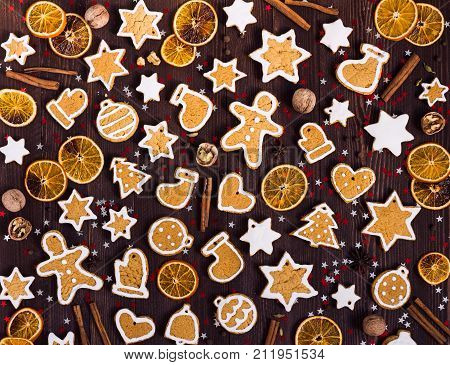 Gingerbread cookies christmas new year oranges cinnamon on wooden table. Festive sweet pastry delicious food. Various cookies gingerbread man star heart christmas ball sock Santa Claus mitten