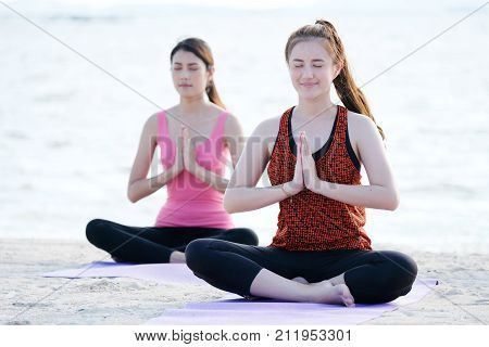 Young healthy asian women practicing yoga in namaste posture on the beach healthy lifestyles wellness well being