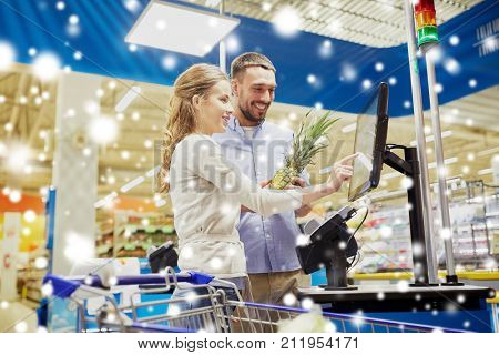shopping, sale, consumerism and people concept - happy couple buying food at grocery store or supermarket self-service cash register over snow