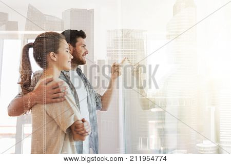 mortgage, people and real estate concept - happy couple looking through window at new home over city buildings background and double exposure effect