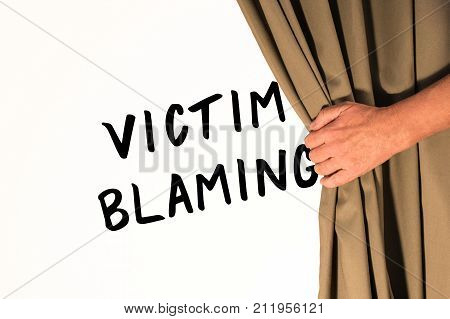 The words Victim Blaming being revealed from behind a curtain