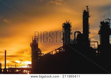 Petrochemical plant on sky sunset Petrochemical plant in silhouette image