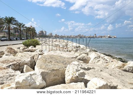 Tyre Lebanon - October 8 2015: Boardwark along the coast of Tyre with the old city and harbour in the background at a sunny day Tyre Sour Lebanon