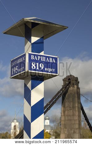 Milepost with names of the cities in Russian and distance in kilometers and the pillars of the suspension bridge in the background