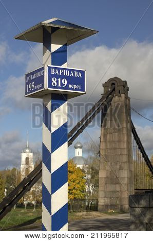 Milepost with names of the cities in Russian and distance in kilometers with the suspension bridge on a background