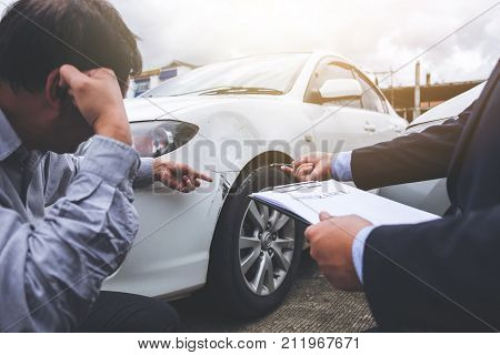 Man agent Filling Insurance Form Near Damaged and examining Car Traffic Accident and insurance concept.