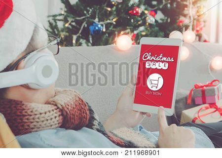 Young Asian man hands holding tablet with Christmas sale screen.Smile face in room with Christmas tree decoration for holiday background.Online shopping concept.