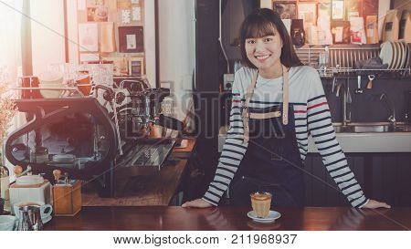 Young beautiful Asian woman barista wear blue apron holding hot coffee cup served to customer at bar counter in coffee shop with smile face.Concept of cafe and coffee shop small business.Vintage tone