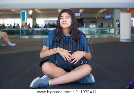 Biracial Asian Caucasian teen girl sitting on airport terminal floor smiling and holding luggage on lap waiting for flight
