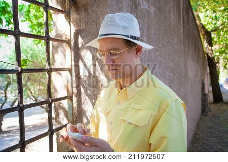 Handsome Caucasian man in early fifties wearing a white hat using cellphone while standing on cobblestone road in Italian town near vineyard