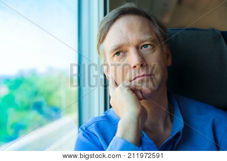 Handsome Caucasian man in early fifties looking out train window thinking while resting head on hand. Commuting businessman thinking on train