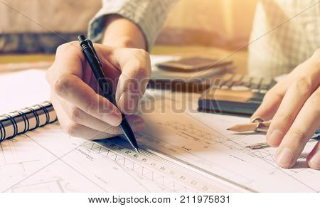 Interior designer or architect reviewing blueprints and holding pencil on desk at home office.