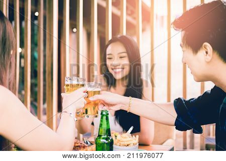Asian People Cheering Beer At Restaurant Happy Hour And Laughing And Talking Together.