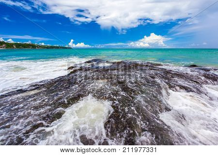 A large dark stone on the seashore covers with a wave and breaks it into foam on a bright sunny day against the backdrop of a colorful sky. Dreamland Beach New, South Kuta, Bali, Indonesia.