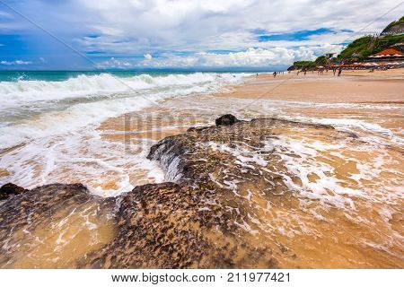 A crowded beach with a big wave falling on a stone and breaking into foam. Dreamland Beach New, South Kuta, Bali, Indonesia.